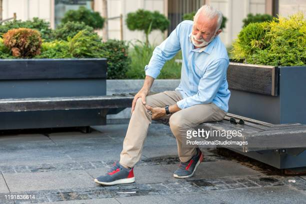 senior businessman with knee problems in the city streets - knee stock pictures, royalty-free photos & images