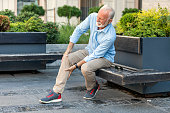 Senior Businessman with Knee Problems in the City Streets