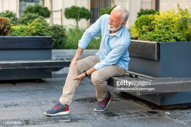 senior businessman with knee problems in the city streets - grief stock pictures, royalty-free photos & images