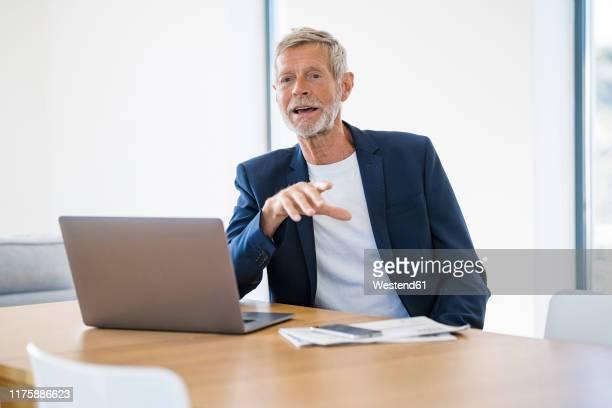 senior businessman with laptop sitting at desk at home talking - ジャケット ストックフォトと画像