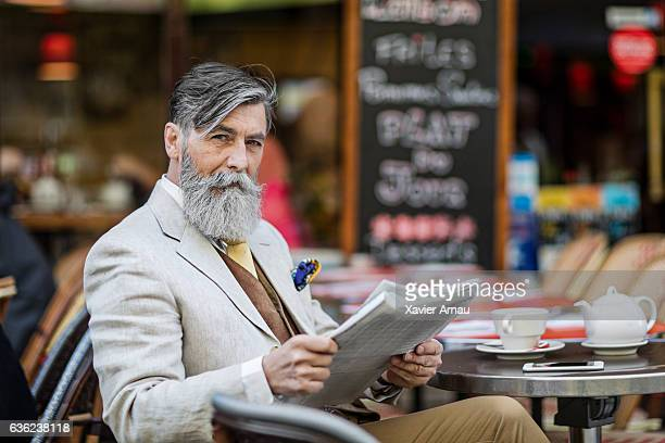 Senior businessman with newspaper at street cafe
