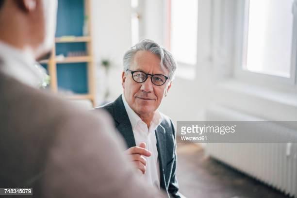 senior businessman with partner in office - variable schärfentiefe stock-fotos und bilder