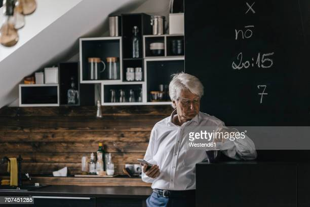 Senior businessman with smartphone and cup of coffee in the kitchen