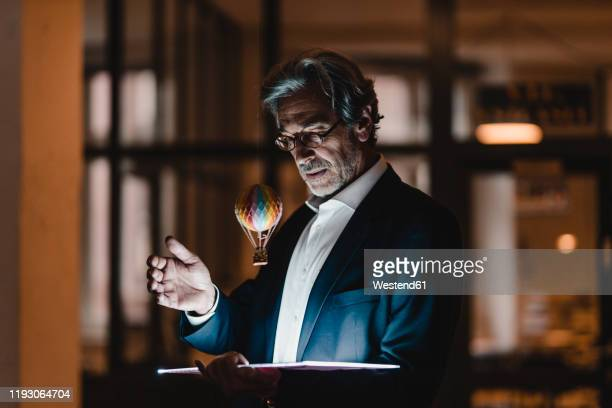 senior businessman with tablet and floating hot-air balloon in office - baby boomer stock-fotos und bilder