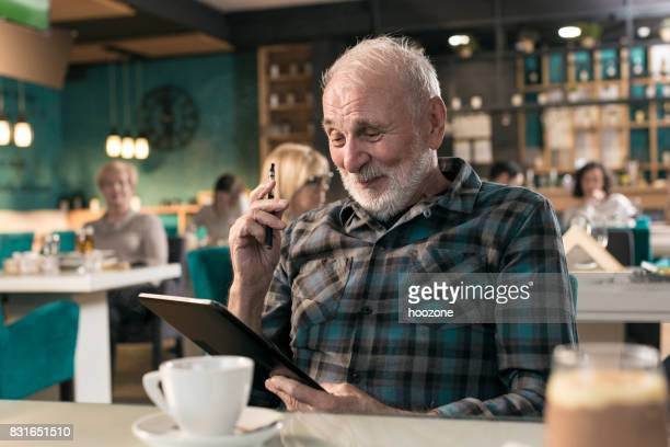 Senior businessman working on digital tablet and wapping in restaurant