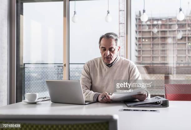 Senior businessman working on laptop in office