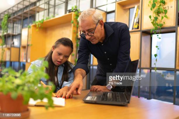senior businessman working together with special needs woman - learning disability stock pictures, royalty-free photos & images