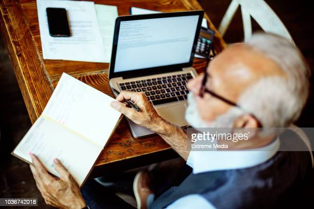 senior businessman writing his agenda - one man only stock pictures, royalty-free photos & images