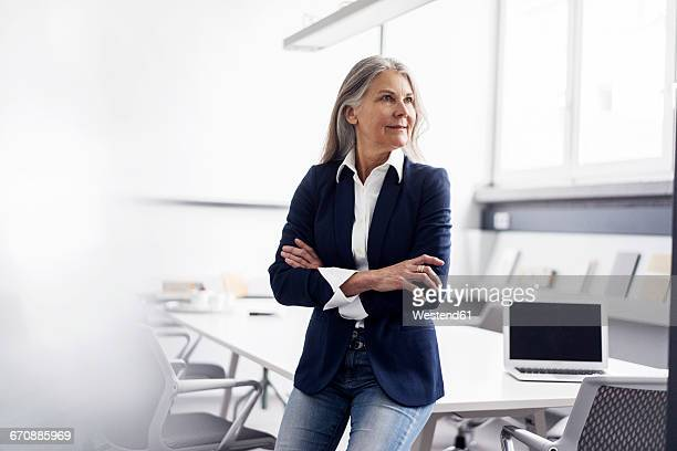 senior businessswoman in conference room - dreiviertelansicht stock-fotos und bilder