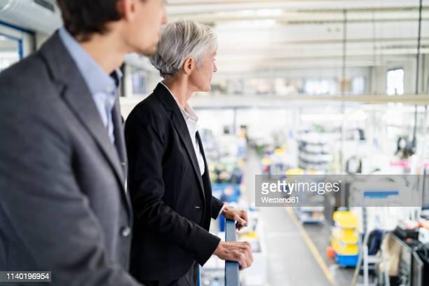senior businesswoman and businessman on upper floor in factory overlooking shop floor - 後任 ストックフォトと画像