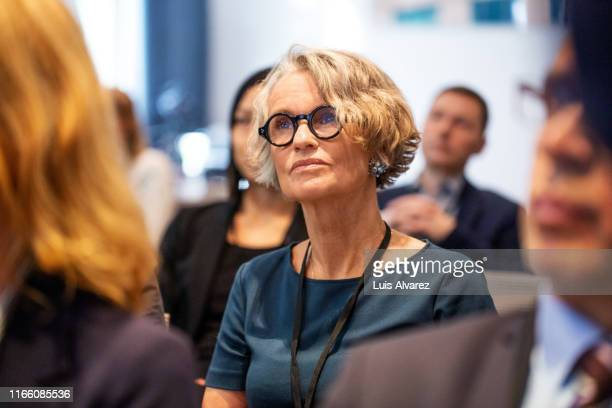 senior businesswoman attending seminar - attending stock pictures, royalty-free photos & images
