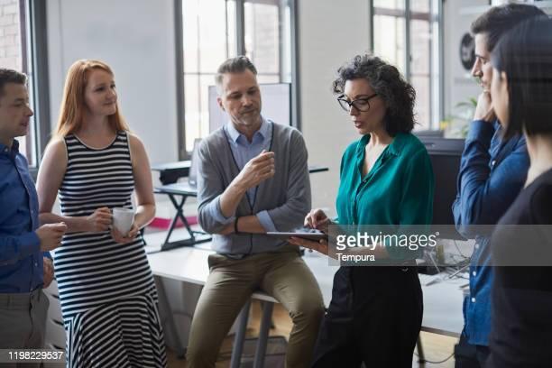 senior businesswoman briefing ihre teamkollegen in einem stand-up-business-meeting. - mitarbeiterengagement stock-fotos und bilder