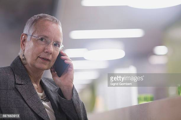 senior businesswoman chatting on smartphone in hotel lobby - sigrid gombert stock pictures, royalty-free photos & images