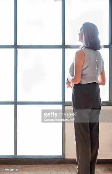 Senior businesswoman gazing through new office window