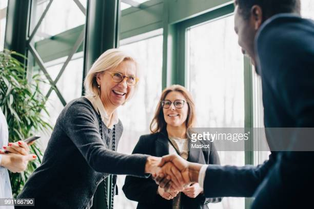 senior businesswoman greeting colleagues during conference - abmachung stock-fotos und bilder