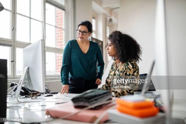 senior businesswoman helping young colleague in office - weibliche führungskraft stock-fotos und bilder
