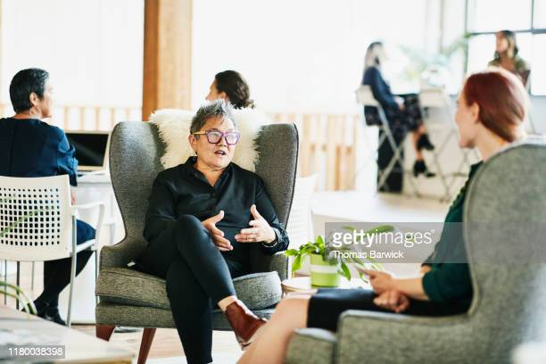senior businesswoman in meeting with client in coworking office - filipino ethnicity and female not male stock pictures, royalty-free photos & images
