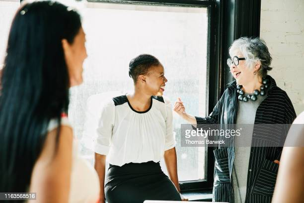 senior businesswoman laughing with colleague during meeting in creative office - idol stock pictures, royalty-free photos & images