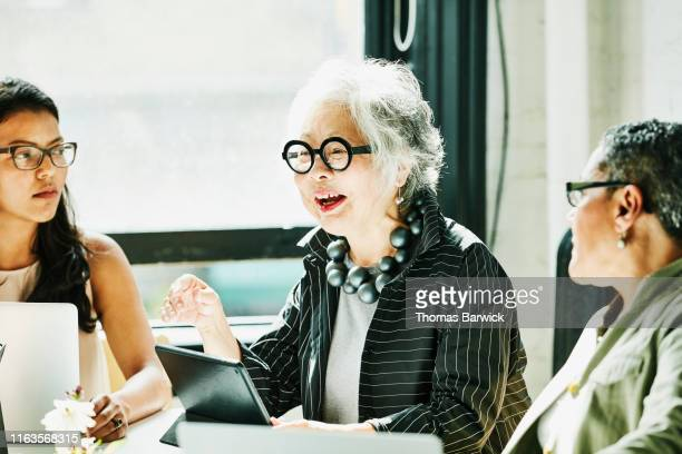 Senior businesswoman leading team meeting in office conference room