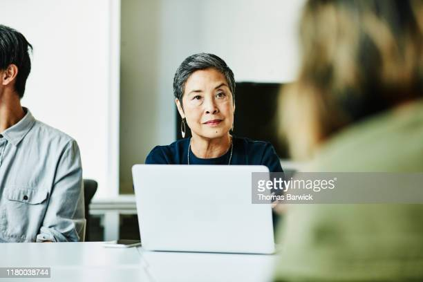 senior businesswoman listening to presentation during meeting in office conference room - disruptaging stock pictures, royalty-free photos & images