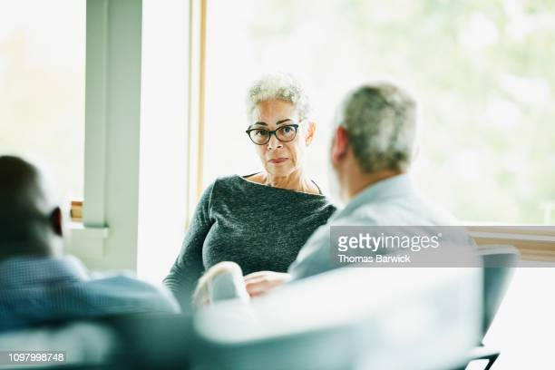 senior businesswoman listening to presentation from coworker during meeting in office - selective focus photos et images de collection
