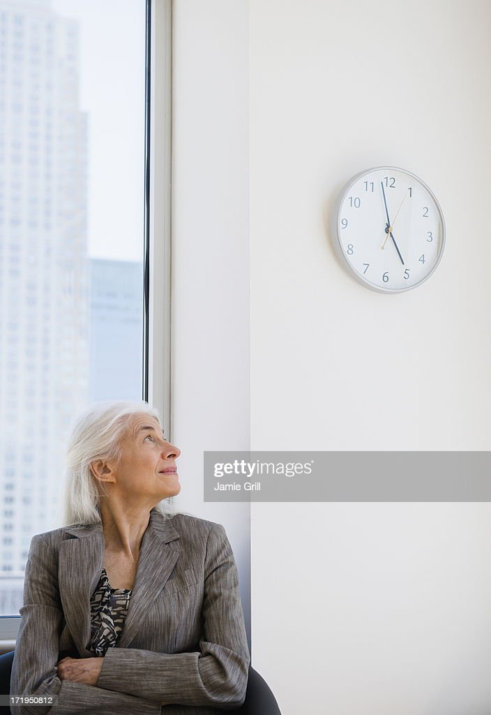 senior businesswoman looking at clock stock photo getty images