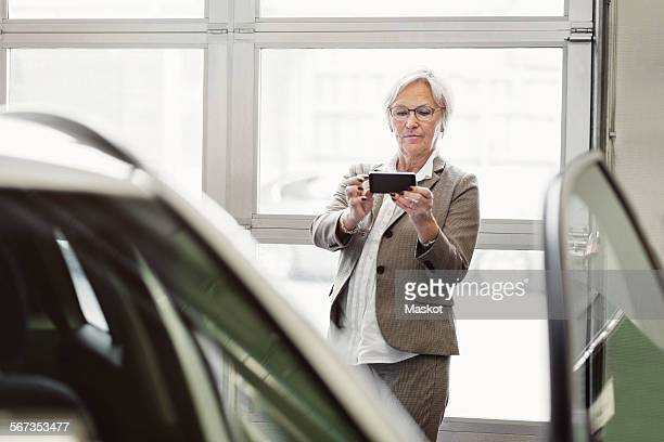 Senior businesswoman photographing car through smart phone in dealership store