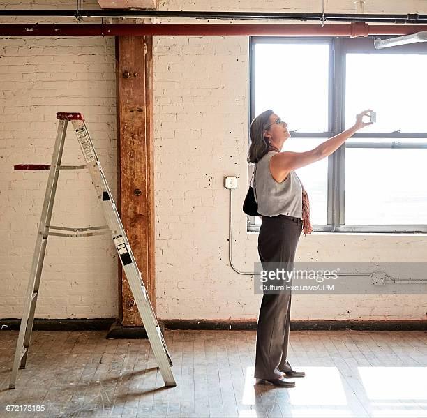 Senior businesswoman photographing empty new office