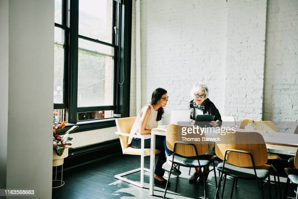 senior businesswoman presenting project on digital tablet to colleague in conference room - two people stock pictures, royalty-free photos & images