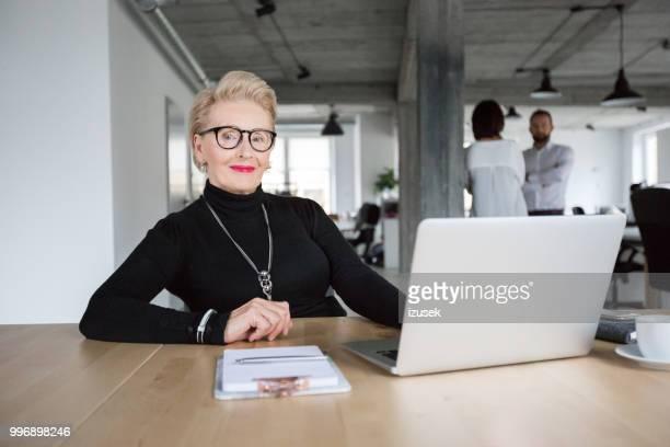 Senior geschäftsfrau sitzt an ihrem Schreibtisch