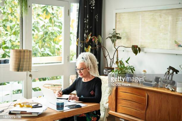 senior businesswoman sitting at table writing notes - greater london stock pictures, royalty-free photos & images
