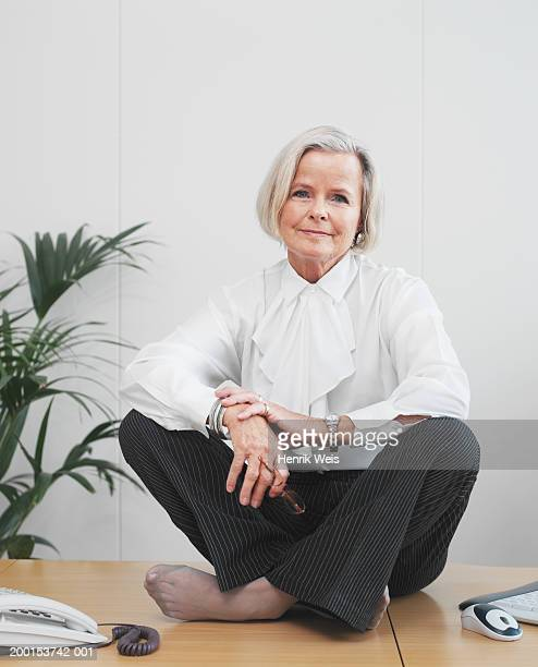 senior businesswoman sitting cross-legged on desk, portrait - old women in pantyhose stock photos and pictures