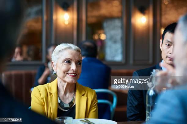 senior businesswoman smiling and looking away during dinner - eleganz stock-fotos und bilder