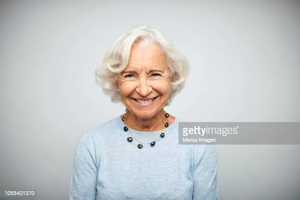 senior businesswoman smiling on white background - bejaard stockfoto's en -beelden