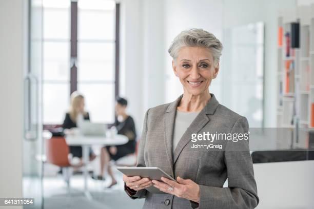 Senior Geschäftsfrau lächelnd in Richtung Kamera hielt digital-Tablette