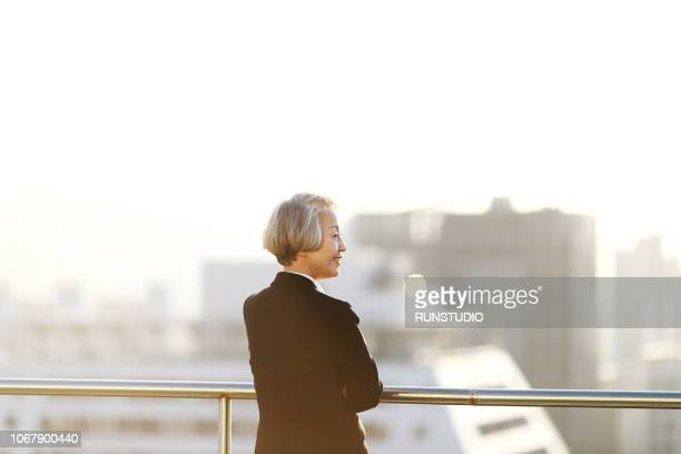 senior businesswoman standing on rooftop - chief executive officer stock pictures, royalty-free photos & images