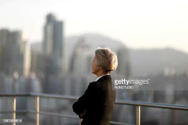 senior businesswoman standing on rooftop - ビジネスウェア ストックフォトと画像