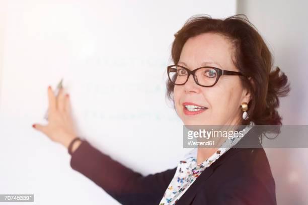 Senior businesswoman talking at flipchart