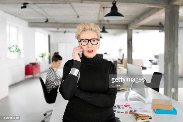 empresaria senior hablando por teléfono en la oficina - izusek fotografías e imágenes de stock