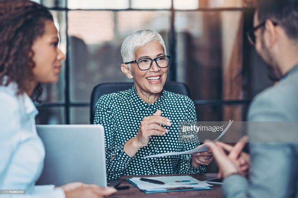 Senior zakenvrouw praat met haar team : Stockfoto