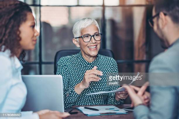 senior businesswoman talking to her team - leadership stock pictures, royalty-free photos & images