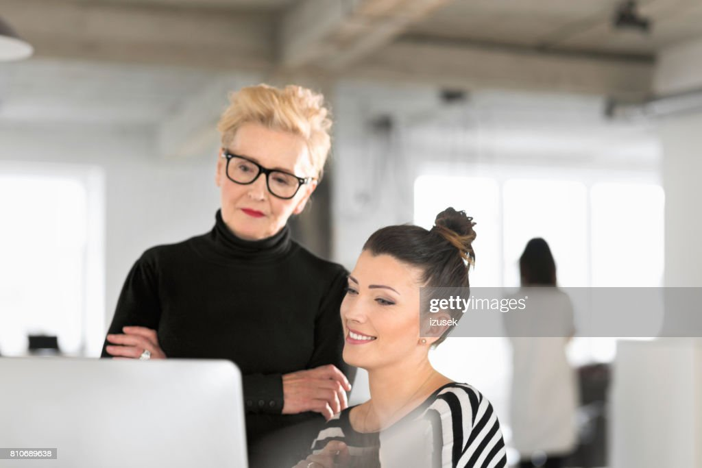 Senior businesswoman talking with creative young woman in the studio : Stock Photo