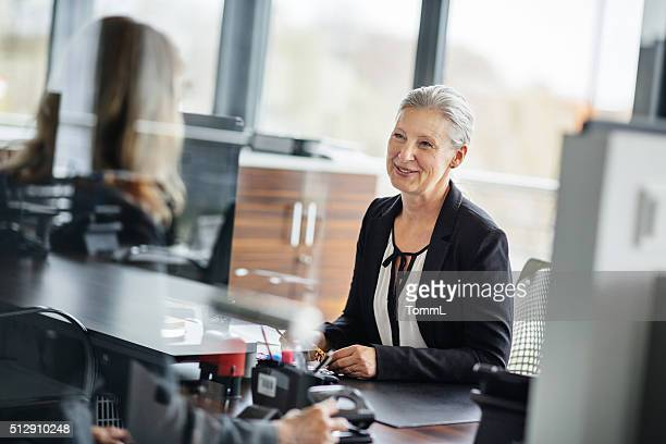 Senior Businesswoman talking with employee