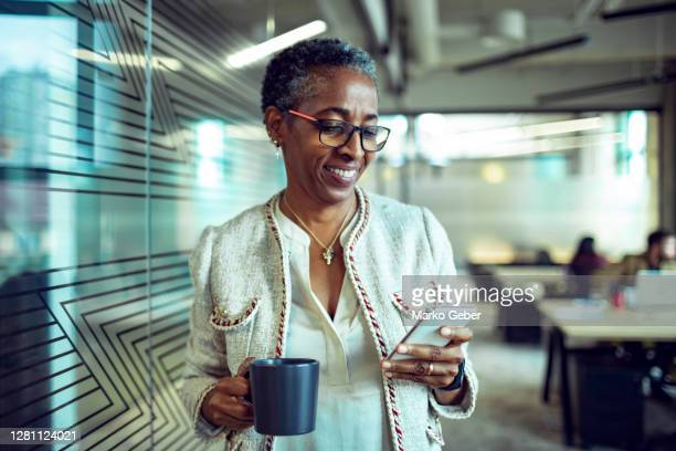senior businesswoman using a phone - businesswoman stock pictures, royalty-free photos & images