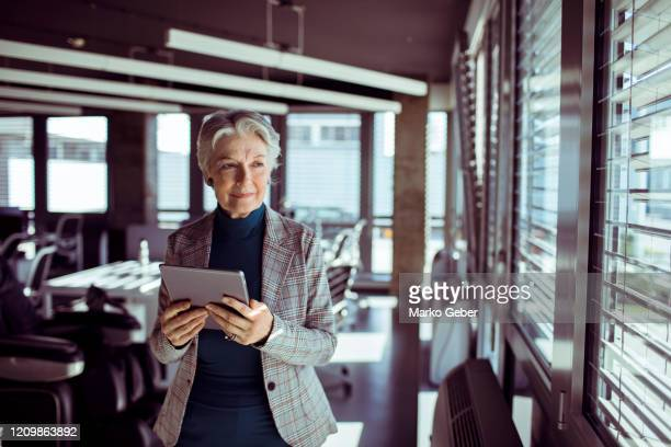 senior businesswoman using a tablet - design professional stock pictures, royalty-free photos & images