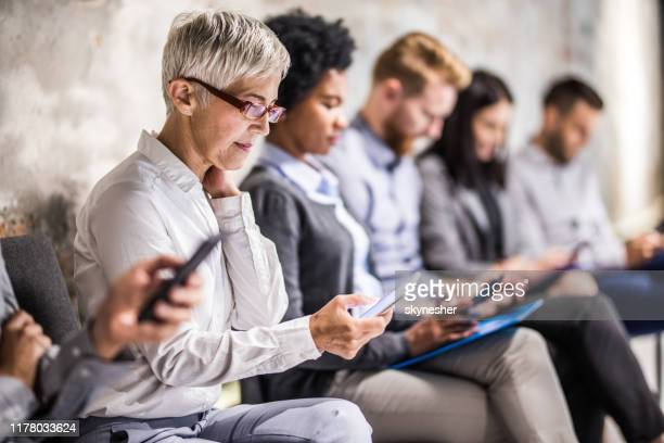 senior businesswoman using cell phone while waiting for job interview. - large group of people stock pictures, royalty-free photos & images