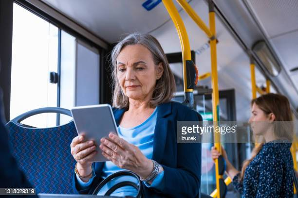 senior businesswoman using digital tablet in bus - izusek stock pictures, royalty-free photos & images