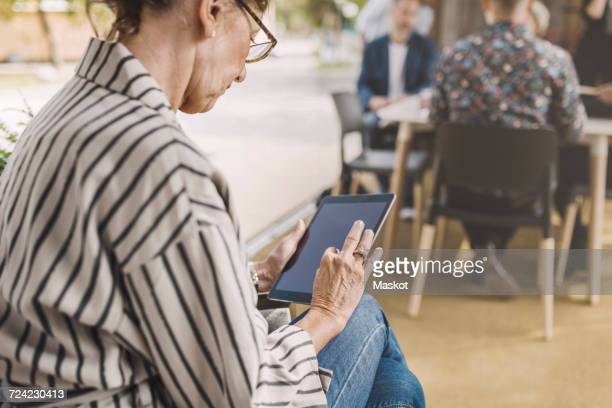 Senior businesswoman using digital tablet in portable office truck