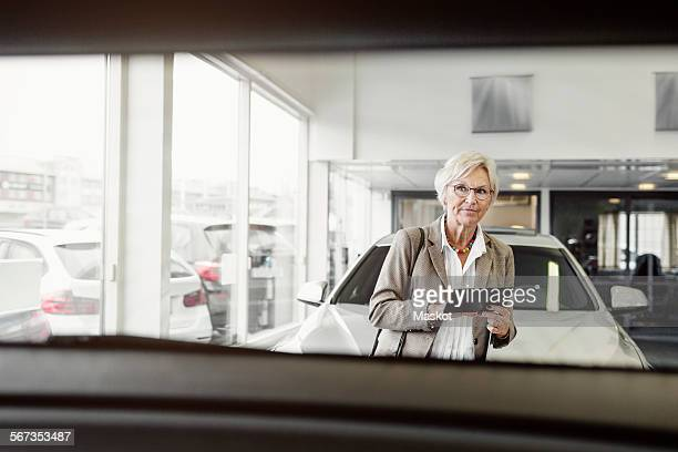 Senior businesswoman with digital tablet looking at car in store