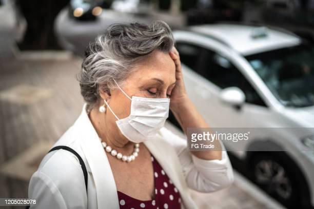 senior businesswoman with mask feeling bad at street - cabeça humana imagens e fotografias de stock
